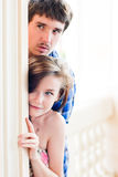 Young happy couple looking round the corner Stock Photo