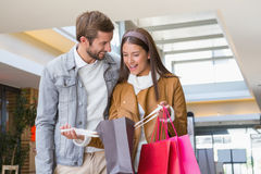 Young happy couple looking at shopping bags Royalty Free Stock Photos
