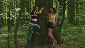 Young happy couple in love carving a heart with their initials on a tree. Green spring forest background.  stock video footage