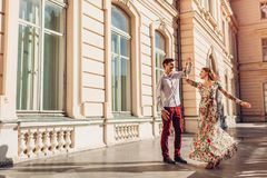 Young happy couple in love dancing by palace outdoors. Man and woman having fun in city. Young happy couple in love dancing by palace outdoors. Man and women stock photos