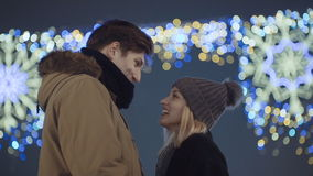 Young happy couple in love enjoying time over evening lights in a city. Happy attractive couple in a christmas market at night. Beautiful bokeh lights stock footage