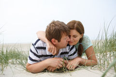 Young happy couple in love having fun on sand dunes of the beach Stock Photo