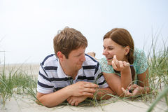 Young happy couple in love having fun on sand dunes of the beach Royalty Free Stock Photo