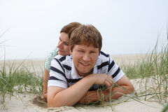 Young happy couple in love having fun on sand dunes of the beach Royalty Free Stock Photos