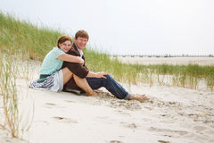 Young happy couple in love having fun on sand dunes of the beach Royalty Free Stock Images