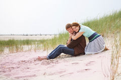 Young happy couple in love having fun on sand dunes of the beach Stock Photography