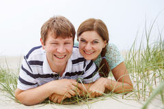 Young happy couple in love having fun on sand dunes of the beach Royalty Free Stock Image