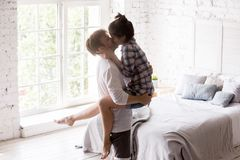 Young happy couple in love at home together. Young happy couple in love spend time together indoors. Husband holding beloved wife on hands kissing in cozy royalty free stock photography
