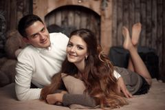 Young happy couple in love lying on rug in cozy wooden interior royalty free stock photos