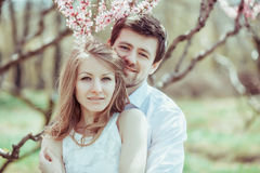 Young happy couple in love outdoors. loving man and woman on a walk at spring blooming park Royalty Free Stock Photos