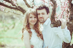 Young happy couple in love outdoors. loving man and woman on a walk at spring blooming park Stock Photos