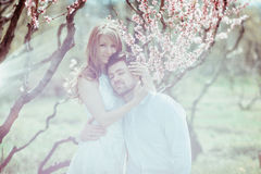 Young happy couple in love outdoors. loving man and woman on a walk at spring blooming park Stock Image