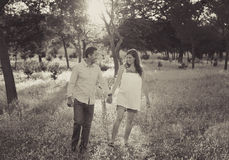 Young happy couple in love together on park landscape sunset with woman pregnant belly stock images
