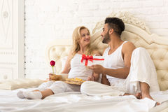 Young Happy Couple Lying In Bed, Hispanic Man Give Woman Surprise Present Envelope With Ribbon, Anniversary Celebration. Lovers In Bedroom Royalty Free Stock Photography