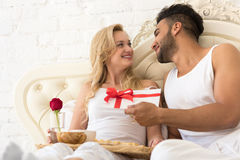 Young Happy Couple Lying In Bed, Hispanic Man Give Woman Surprise Present Envelope With Ribbon, Anniversary Celebration Stock Image