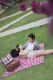 Young happy couple lying on a blanket together while having a picnic in the park, blossoms in the foreground Stock Images