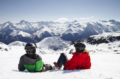 Young happy couple lying in snowy mountains Stock Photos