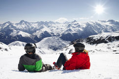 Young happy couple lying in snowy mountains Stock Image