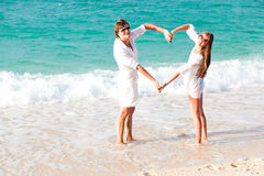 Young happy couple making heart shape at  beach. Royalty Free Stock Photography