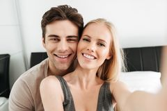 Young happy couple making selfie while lying in bed Stock Photography