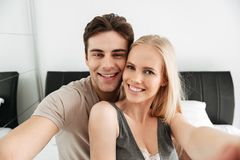 Young happy couple making selfie while lying in bed Stock Images