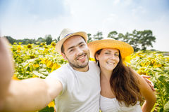 Young happy couple man and woman are in a field of sunflowers, make selfie pics Stock Images
