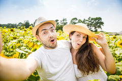 Young happy couple man and woman are in a field of sunflowers, make selfie pics Royalty Free Stock Image