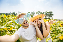 Young happy couple man and woman are in a field of sunflowers, make selfie pics Royalty Free Stock Images