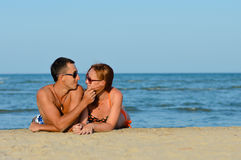 Young happy couple man and woman lying on sandy beach. Happy couple men and women having fun lying on sandy beach Stock Photo
