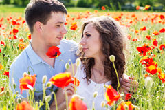 Young happy couple on a meadow full of poppies. Love. Young happy couple reasting on a meadow full of poppies Stock Image