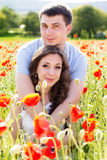 Young happy couple on a meadow full of poppies Stock Images