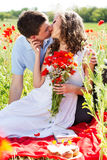 Young happy couple on a meadow full of poppies. Young happy couple reasting on a meadow full of poppies Stock Photography