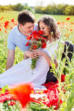 Young happy couple on a meadow full of poppies Royalty Free Stock Photo
