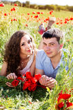 Young happy couple on a meadow full of poppies Royalty Free Stock Image