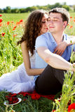 Young happy couple on a meadow full of poppies Royalty Free Stock Photos