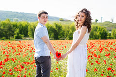 Young happy couple on a meadow full of poppies Stock Photography