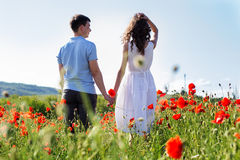 Young happy couple on a meadow full of poppies Stock Photos