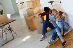 Young happy couple moving in new home and unpacking boxes Stock Photos