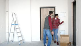 Young happy couple moving in to their new home and they joyful dancing next to boxes. 3840x2160 stock video footage