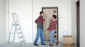 Young happy couple moving in to their new home and they dancing next to boxes. 3840x2160 stock footage