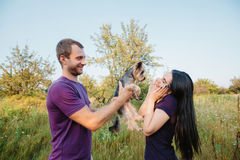 Young happy couple on nature,the boy gives girl a dog - yorkshire terrier as gift Royalty Free Stock Photos