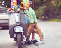 Young happy couple near the old retro scooter in a city street. Stock Photos