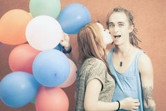 Young happy couple near the orange wall stand with balloons Royalty Free Stock Image