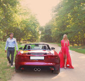 Young happy couple near the red car Royalty Free Stock Image