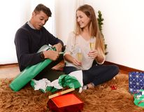 Young Happy Couple opening Xmas presents Royalty Free Stock Photos