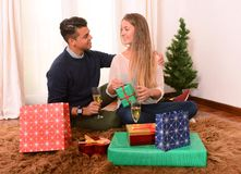 Young Happy Couple opening Xmas presents Royalty Free Stock Image