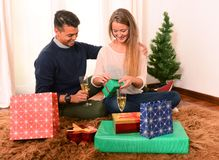 Young Happy Couple opening Xmas presents Stock Photography