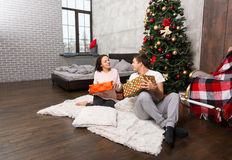 Young happy couple in pajamas rejoice at their presents while si Stock Photography