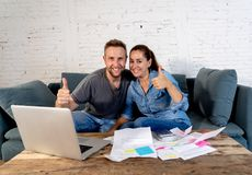 Young happy young couple paying bills with laptop feeling fortunate and lucky off debts royalty free stock photo