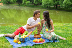 Young happy couple picnicking outdoors near the Stock Photos